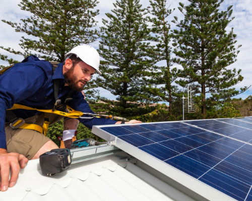 roofing contractor inspecting solar panels recently installed in colorado