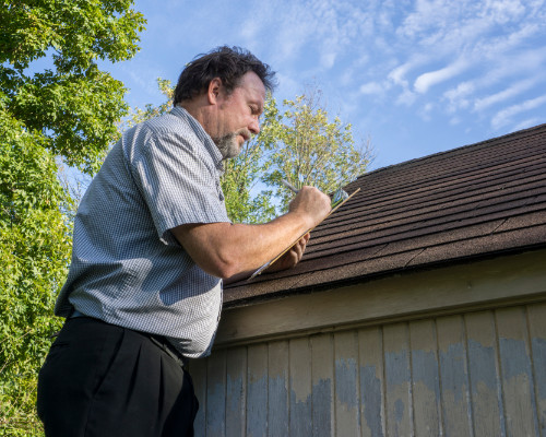roofer documenting hail damage for an insurance claim